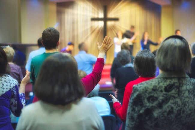Christian congregation worship God together, with cross with light rays in background